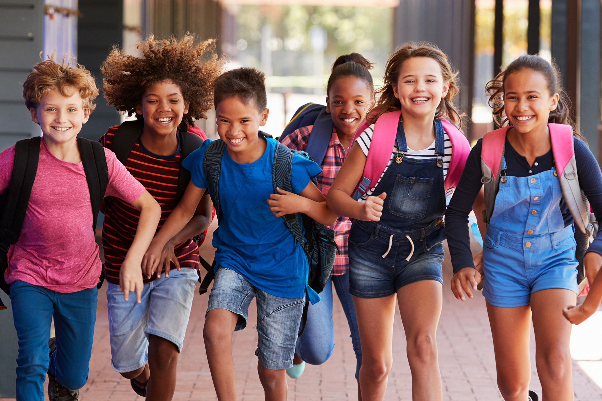 Diverse students happily running in school