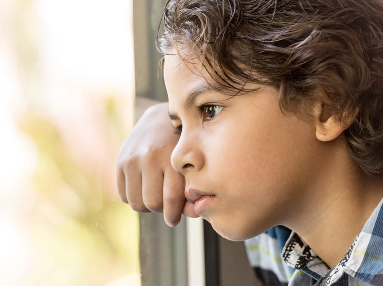 boy looking out the window pensively