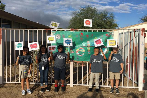 Elementary school students holding Start With Hello Week signs