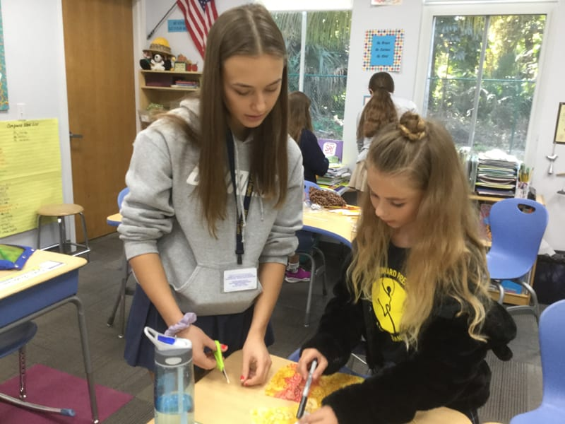 Lena, a member of the Youth Advisory Board, helps an elementary school student create a doll as part of a recent diversity exercise.