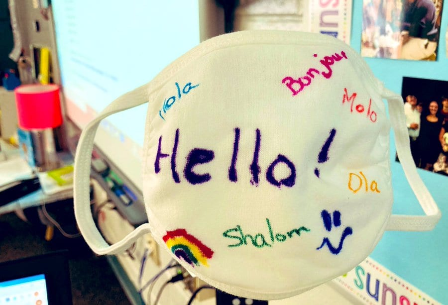 """Students decorate a mark with the word """"hello"""" in colorful ways in multiple languages."""