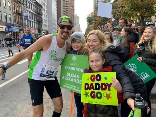 Sloan Alexander at the NYRR Marathon being cheered on by his family.