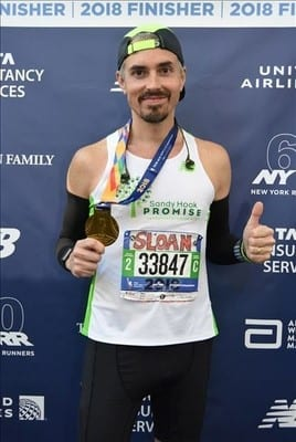 Sloan shows off his medal for finishing the NYC Marathon in 2018.