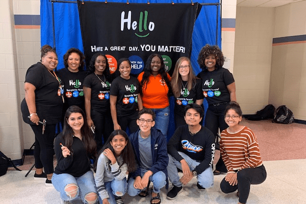 """A SAVE Promise Club stands in front of a banner that says """"Hello, Have a great Day! You Matter!"""