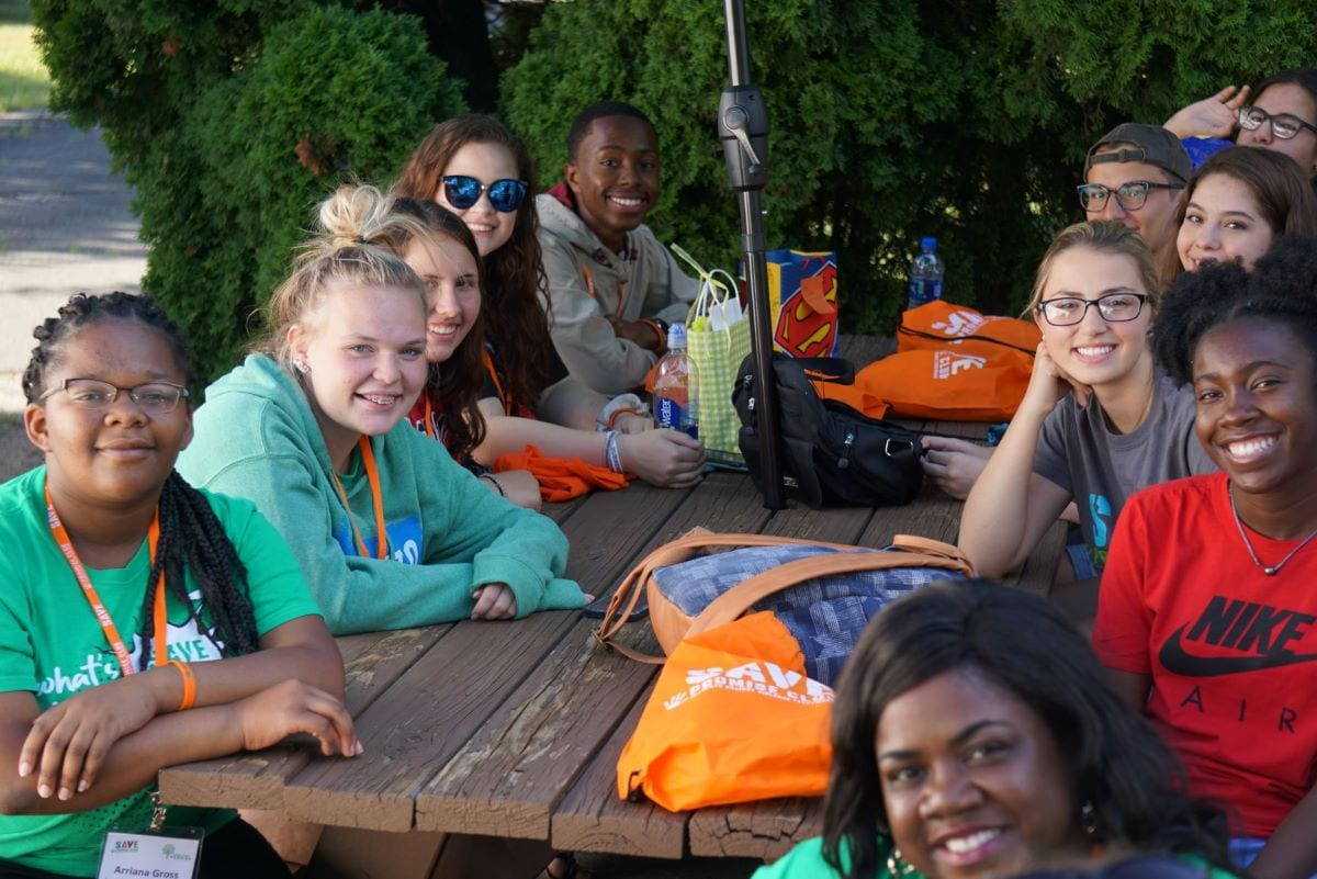 Arriana Gross and other members of our National Youth Advisory Board gather around a picnic table.