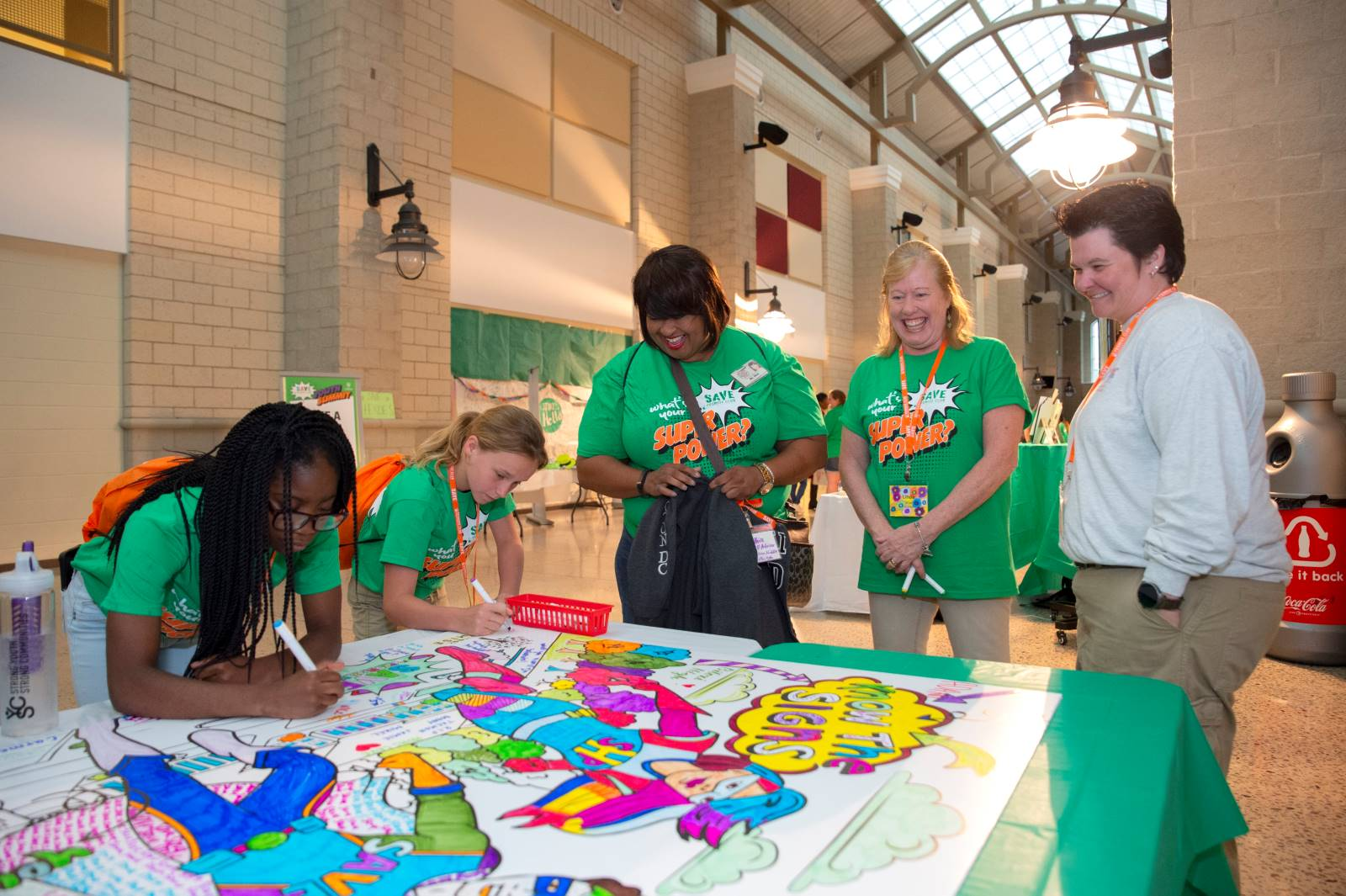 Students participating in the National SAVE Promise Club Youth Summit in 2019 write multi-colored messages of kindness to their peers.